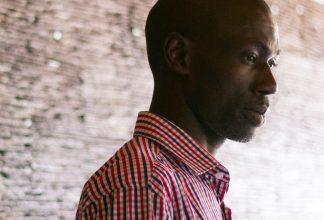 Edmund Yakani står mot tegelvägg
