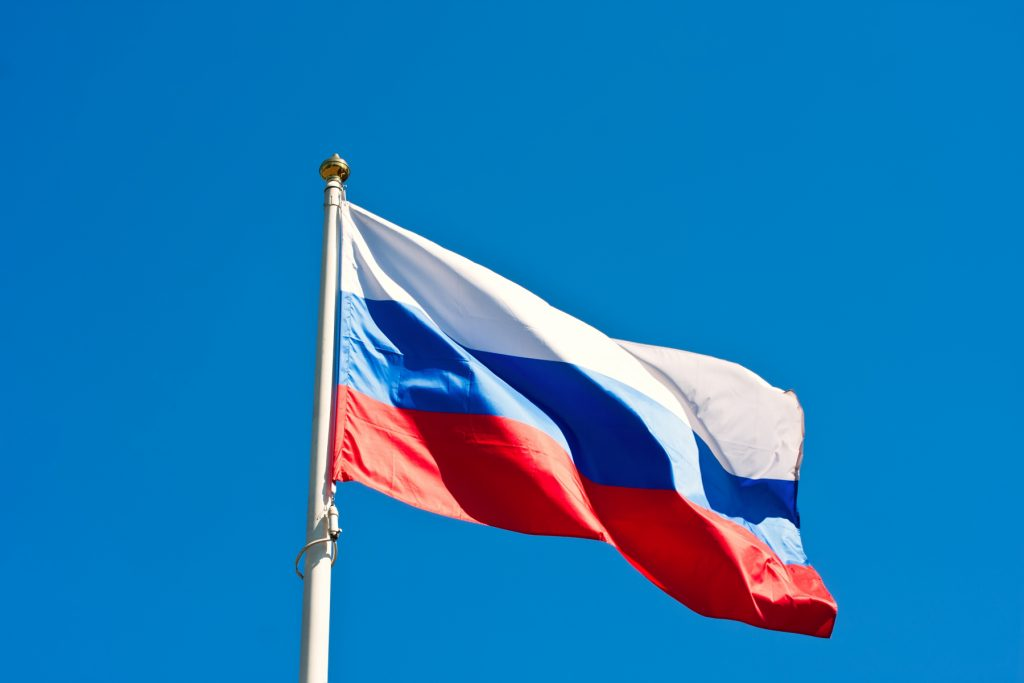 The picture consist of the flag of Russia with a background of a clear blue sky.