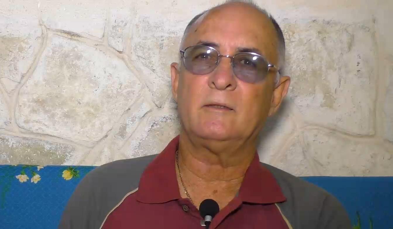Roberto de Jesús Quiñones Haces in front of a grey background