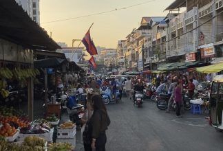 Crowded street and waiving flags in Cambodia
