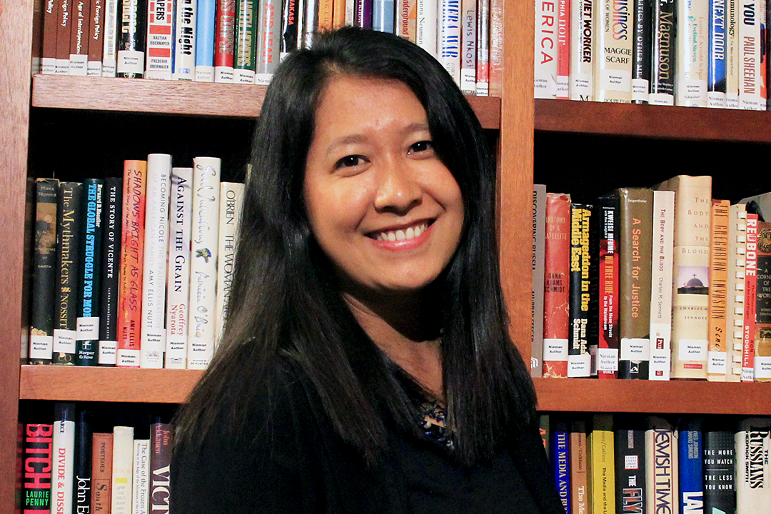Esther Htu San står framför en stor bokhylla fylld av böcker och ler.