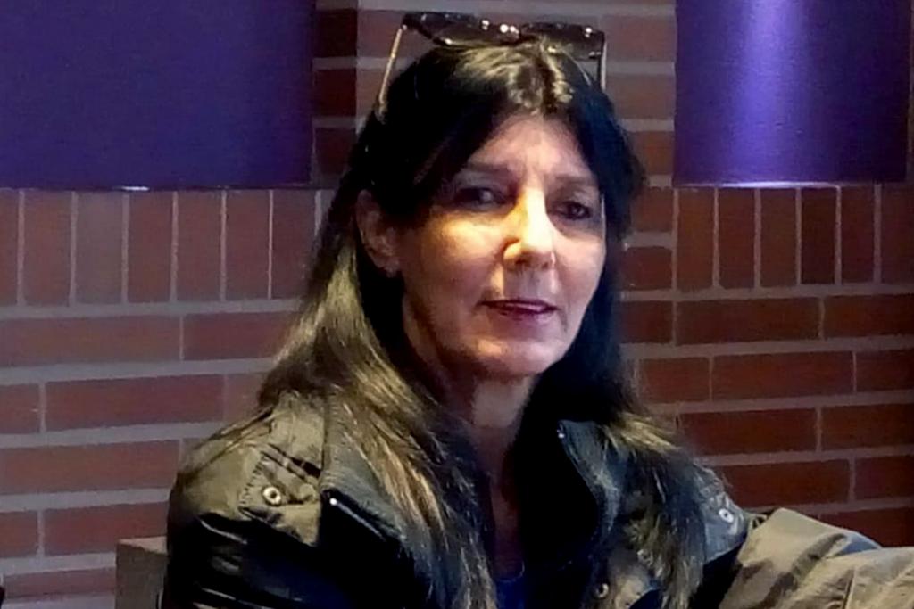 María Elena Mir Morrero in front of a brick wall.