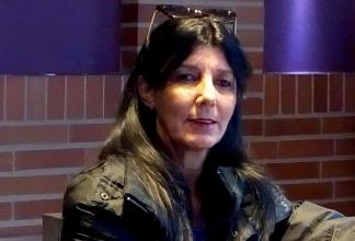 María Elena Mir Morrero sitter framför en tegelvägg i en skinnjacka.