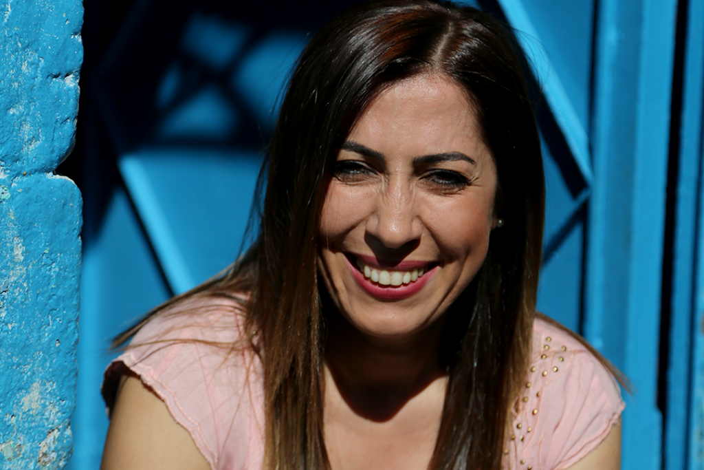 Nurcan Baysal, smiling in fornt of a blue wall.