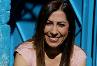 Nurcan Baysal sitter framför en blå vägg och ler.