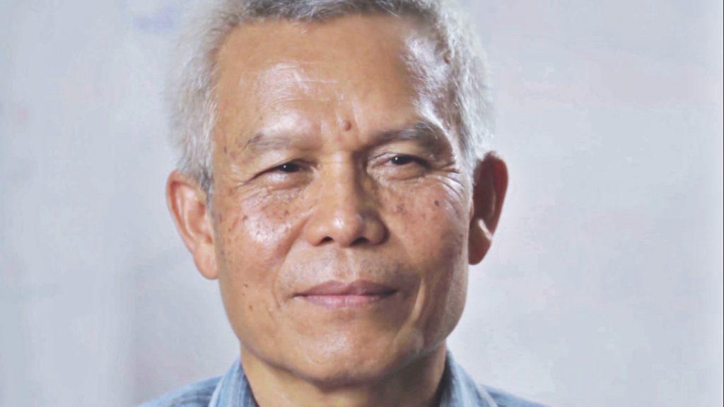Porträtt av Sombath Somphone mot grå bakgrund