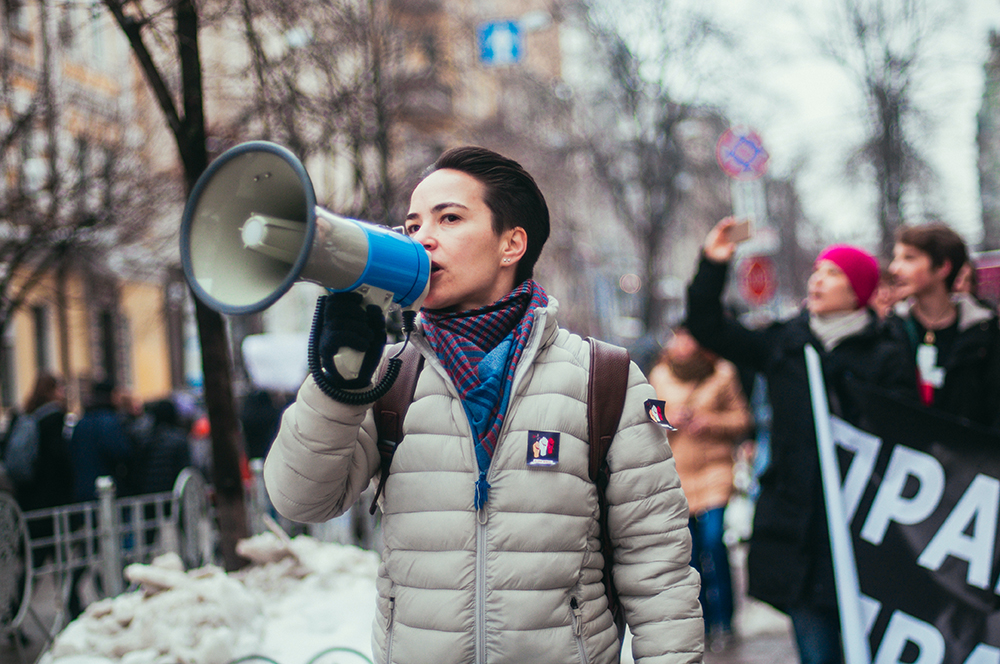 Olena Shevchenko speaking in a megaphone during a demonstration.